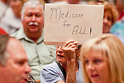 Aug, 25, 2009 -- SUN CITY, AZ: RIVKO KNOX, from Phoenix, holds up a sign supporting health care reform during the Town Hall meeting on health care sponsored by Sen John McCain at Grace Bible Church in Sun City, AZ, Tuesday. More than 1,000 people attended the meeting in the church, which seats 700. Sun City is a staunchly Republican suburb of Phoenix and most of the crowd was opposed to President Obama health care reform efforts. Knox was one of only a handful of people at the meeting who support the president's health care reform efforts.  Photo by Jack Kurtz