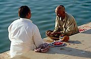 A priest performs a personal Hindu pooja ceremony on the ghats of the Holy Lake at Pushkar, Rajasthan, India