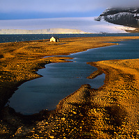 FRANZ JOSEF LAND, RUSSIA. Eira Lodge on Bell Island & glacier on Mabel Island.  Site of over-wintering by explorer Leigh Smith in 1881. (Arctic Ocean).