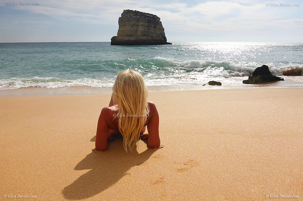 A blonde woman relaxing on a golden yellow sandy beach in the summer at Caneiros, Algarve, Portugal, watching the Atlantic waves crash on the shoreline with a limestone sea stack in the distance.