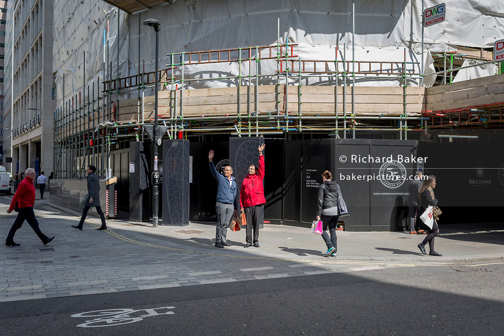 Two men stand on a street corner and wave to a colleague, on 19th April, in the City of London, England.