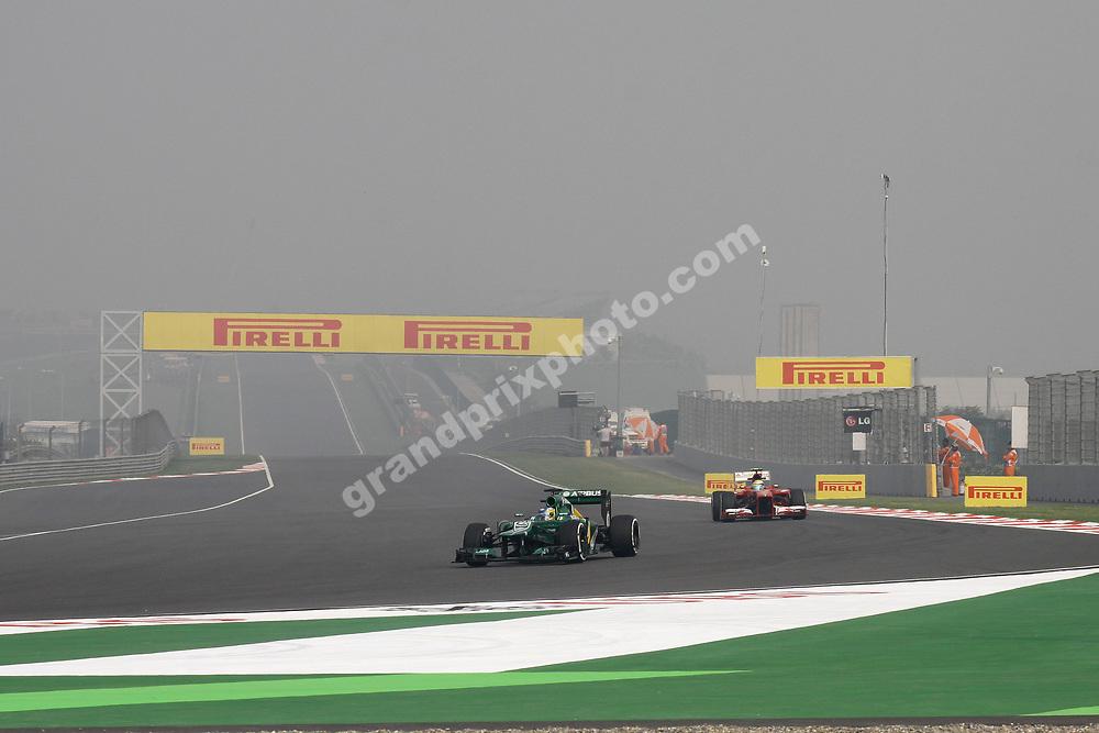 Charles Pic (Caterham-Renault) and Felipe Massa (Ferrari) in foggy practice  at the 2013 Indian Grand Prix at the Buddh International Circuit  outside Delhi. Photo: Grand Prix Photo