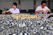 KUNMING, CHINA - (CHINA OUT) <br /> <br /> Making Reparation With 100,000 Coins<br /> <br /> Employees deal with one-jiao coins at a branch of Industrial and Commercial Bank of China Ltd. (ICBC) in Kunming, Yunnan Province of China. Mrs. Wu and her husband were beaten by three waiters in front of a restaurant after they finished their meal. Mrs. Wu had an argument with the waiters as the bowl was not clean. Mrs. Wu and her husband stayed in the hospital for a month. Afterward, Mrs. Wu sued the restaurant and won the case. The court decided that the defendant should pay the plaintiff 68,000 yuan in compensation. The restaurant paid 38,000 yuan at the first time. On August 9 this year, the restaurant sent eight bags of one-jiao coin, 100,000 in total, to Mrs. Wu. One jiao is equal to one-tenth of a yuan. It took eight hours for 18 bank clerks to successfully sort out 5,000 yuan.<br /> ©Exclusivepix