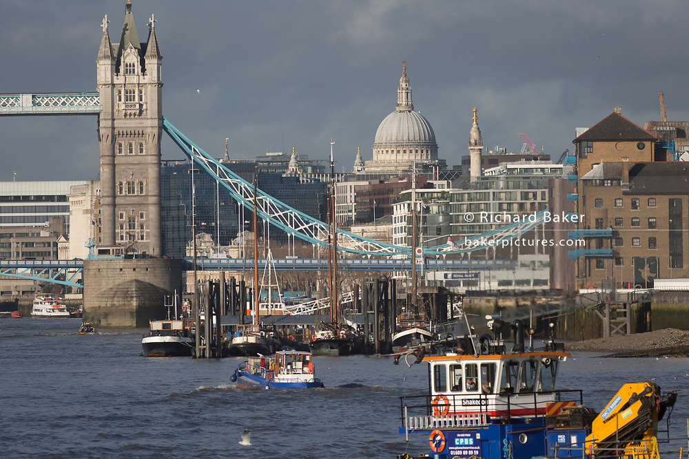River traffic uses the Thames as a water highway with St. Paul's Cathedral, the Monument and Tower Bridge in the distance, on 17th January 2020, in London, England.