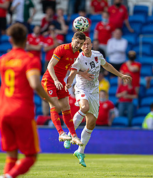 CARDIFF, WALES - Saturday, June 5, 2021: Wales' Ben Davies (L) challenges for a header with Albania's Bekim Balaj during an International Friendly between Wales and Albania at the Cardiff City Stadium in their game before the UEFA Euro 2020 tournament. (Pic by David Rawcliffe/Propaganda)