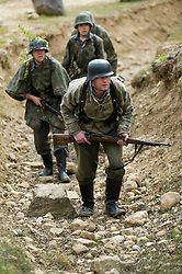 Carrying Mauser K98's and wearing splinter patteen camouflage with the the iconic coal scuttle helmet or stahlhelm, Reenactors from Northern World War Two Association take part in a 24 hour  private exercise, held at Sutton Grange, near Ripon in Yorkshire<br />