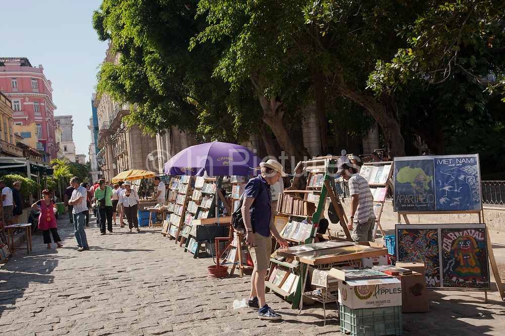 Man looks at books in the market. Placa de Armas - Weapons Square in Havana old town has a dailt book market that also sells some memorabilia. Many of the books are old due to the tight restrictions of the media in Cuba.
