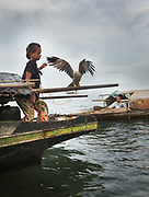 Inda Mulla's relatives living all year round on a Lepa, a traditional houseboat. Keeping a bird as a pet on her boat.
