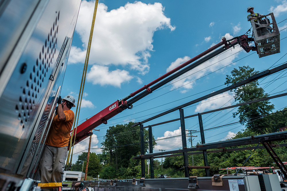 Cheve Tolbert (cq) left, works with Rick Handy, in an extension bucket at right, to attache an LED panel to a crane while technicians from Lamar Advertising install a digital billboard structure along Wards Road in Lynchburg, VA Wednesday, August 29, 2018. U.S. companies are investing in re-training efforts to fill a slew of open positions as a tight labor market and changing job requirements makes it hard to find qualified staffers.<br /> CREDIT: Justin Ide for The Wall Street Journal<br /> RETRAIN