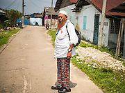 01 JUNE 2015 - KULAI, JOHORE, MALAYSIA:  MOHAMED SHAFI bin HABE, a prominent member of the Rohingya community in Kulai, Malaysia, walks through a neighborhood that houses more than 100 Rohingya refugees in Kulai. The UN says the Rohingya, a Muslim minority in western Myanmar, are the most persecuted ethnic minority in the world. The government of Myanmar insists the Rohingya are illegal immigrants from Bangladesh and has refused to grant them citizenship. Most of the Rohingya in Myanmar have been confined to Internal Displaced Persons camp in Rakhine state, bordering Bangladesh. Thousands of Rohingya have fled Myanmar and settled in Malaysia. Most fled on small fishing trawlers. There are about 1,500 Rohingya in the town of Kulai, in the Malaysian state of Johore. Only about 500 of them have been granted official refugee status by the UN High Commissioner for Refugees. The rest live under the radar, relying on gifts from their community and taking menial jobs to make ends meet. They face harassment from Malaysian police who, the Rohingya say, extort bribes from them.       PHOTO BY JACK KURTZ