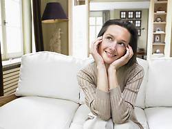 Apr. 24, 2007 - Woman sitting on sofa in living room smiling.. Model and property Released (MR&PR) (Credit Image: © Cultura/ZUMAPRESS.com)