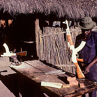A soldier at the UNITA rebel headquarters in Jamba  during the Angola Civil War makes replica AK-47's out of elephant ivory. UNITA killed thousands of elephants and sold ivory to buy arms. 1988