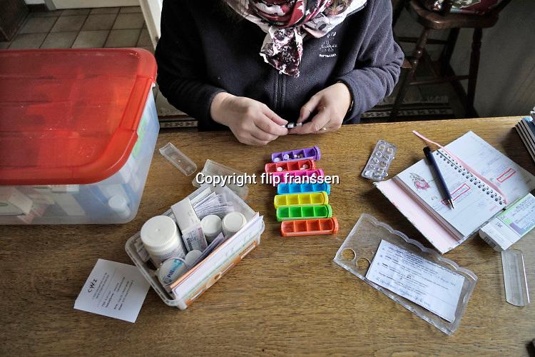Nederland, Nijmegen, 8-1-2019 Een vrouw met een auto immuunziekte vult haar pillendoosje met zeven vakjes met medicijnen voor de dagen van de week. Foto: Flip Franssen