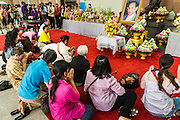 09 OCTOBER 2014 - BANGKOK, THAILAND: People pray for Bhumibol Adulyadej, the King of Thailand in the lobby of Siriraj Hospital. The King has been hospitalized at Siriraj Hospital since Oct. 4 and underwent emergency gall bladder removal surgery Oct. 5. The King is also known as Rama IX, because he is the ninth monarch of the Chakri Dynasty. He has reigned since June 9, 1946 and is the world's longest-serving current head of state and the longest-reigning monarch in Thai history, serving for more than 68 years. He is revered by the Thai people and anytime he goes into the hospital thousands of people come to the hospital to sign get well cards.   PHOTO BY JACK KURTZ
