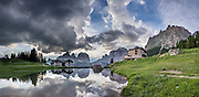 A pond reflects Hotel Gonzaga and peaks of the Langkofel Group (Sassolungo, 3181 meters / 10,436 feet) and Sella Group, in Val di Fassa, 2 km west of Passo Pordoi, in the Dolomites, Trentino-Alto Adige/Südtirol region, Italy. We highly recommend lodging in a pristine, roomy apartment with full kitchen in a beautiful setting at Hotel Gonzaga Appartamenti Garni (Canazei, I-38032, Streda de Pordoi, 102, telephone +39 0462 602121). The Dolomites are part of the Southern Limestone Alps, Europe. UNESCO honored the Dolomites as a natural World Heritage Site in 2009. This panorama was stitched from 5 overlapping photos.