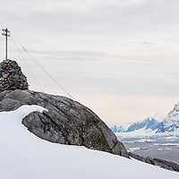 A stone cairn with cross was erected by the French Antarctic explorer Jean-Baptiste Charcot in 1904 and now looks out over Port Charcot on Booth Island, Antarctica.