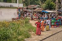 Sri Lankan women wait as a train passes