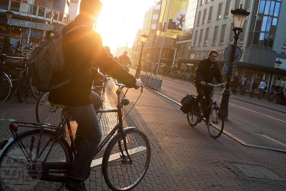 Fietsers in het avondlicht bij de Potterstraat in Utrecht.<br /> <br /> Cyclists at twilight in Utrecht.