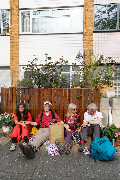 © Licensed to London News Pictures. 17/04/2019. Environmental activists from the Extinction Rebellion movement glue and fix themselves together as they sit outside the Labour Party leader's home in north London as part of a series of direct actions taking place across the capital. The protests demand urgent action from governments on climate change. Photo credit: Vickie Flores/LNP