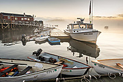Lobstermen prepare to head out on the water during a foggy morning sunrise at Five Islands Harbor, Maine.
