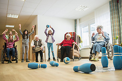 Girls playing bowling with senior women in rest home
