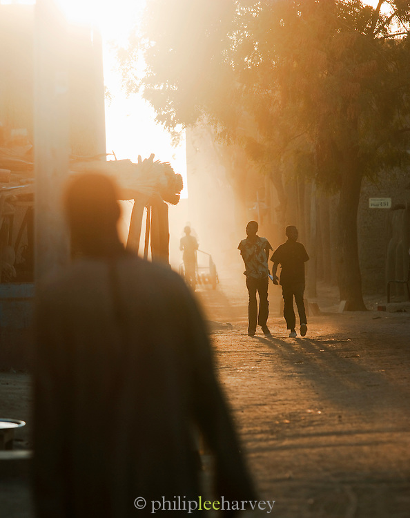 People in the dusty streets at dusk in Djenné, Mali