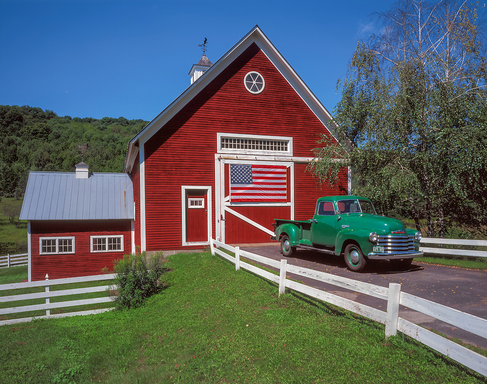 Red barn with America flag and antique GMC pickup truck circa 1953, East Pomfret, VT