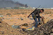 Mcc0030300 . Daily Telegraph..A Libyan rebel volunteer near the wealthy oil town of Ras Lanuf, looking for ammunition amongst abandoned ammo crates ..Gaddafi's forces have been on forced retreat since saturday night due to repeated attacks from NATO airstrikes...Ras Lanuf 27 March 2011