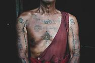 Mandalay, Myanmar - November 9, 2011: A 71-year-old Burmese monk and his tattoos at a Buddhist  monastery Mandalay, Myanmar.