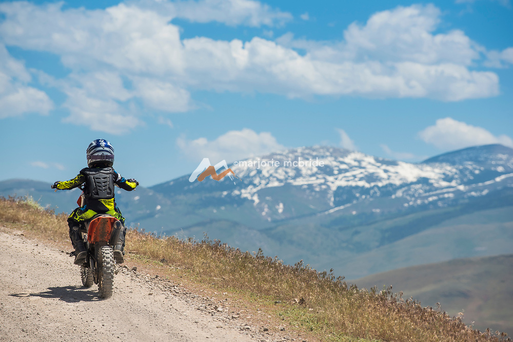 Little boy riding dirt bike on Trapper Creek Road along the Lower Goose Creek Reservoir with view of snow capped mountains beyond during spring near Oakley, Idaho. MR