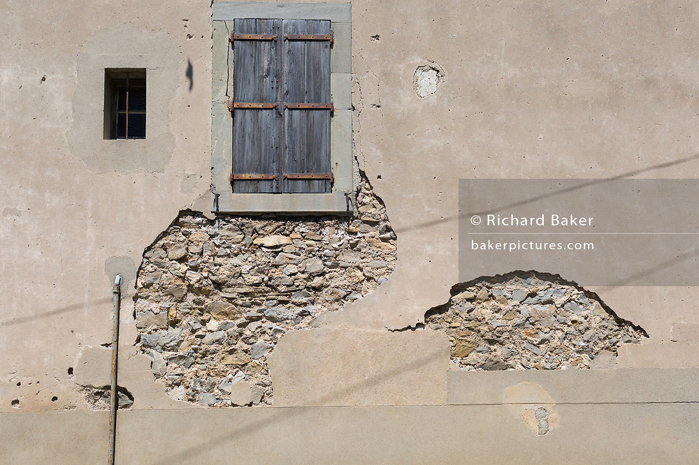 Detail of a plaster-rendered village wall, on 25th May, 2017, in Homps, Languedoc-Rousillon, south of France