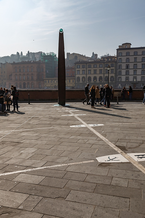 The monumental sundial in Florence, Italy. The glass polyhedron atop the large bronze gnomon casts the shadow that indicates the date and an actual solar time. Regarding the meantime shown in the wristwatches, the actual solar time has a periodic variation that can exceed a quarter of an hour.