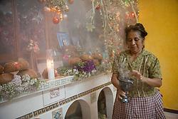 North America, Mexico, Oaxaca Province, Teotitlan del Valle, woman with burner of copal incense at altar (ofrenda) during Day of the Dead (Dias de los Muertos) celebration
