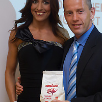 """Norbert """"Norbi"""" Schobert (R) and his wife Reka Rubint (L) pose with a pack of sugar for a photo during a press conference of his franchise called Update in Budapest, Hungary on May 18, 2010. ATTILA VOLGYI"""