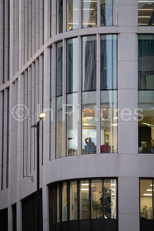 On the first day of the government's second national Coronavirus lockdown, a woman is seen from the rear in a corporate office near London Bridge in the capital's financial district, the Square Mile, on 5th November 2020, in London, England. Most workers are still working from home and the continuing pandemic restrictions are damaging small buinesses and the wider UK economy. The current lockdown is to last at least 4 weeks in the run-up to Christmas.