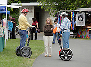 Hamptonburgh, New York - An elderly couple using Segways talks to a woman at the fourth annual Earth & Water Festival at Thomas Bull Memorial Park on June 4, 2011. Segways are two-wheeled, self-balancing electric vehicles invented by Dean Kamen.
