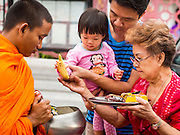 "21 JULY 2013 - BANGKOK, THAILAND:   Three generations of a family give food to a monk to make merit at Wat Benchamabophit on the first day of Vassa, the three-month annual retreat observed by Theravada monks and nuns. On the first day of Vassa (or Buddhist Lent) many Buddhists visit their temples to ""make merit."" During Vassa, monks and nuns remain inside monasteries and temple grounds, devoting their time to intensive meditation and study. Laypeople support the monastic sangha by bringing food, candles and other offerings to temples. Laypeople also often observe Vassa by giving up something, such as smoking or eating meat. For this reason, westerners sometimes call Vassa the ""Buddhist Lent.""        PHOTO BY JACK KURTZ"