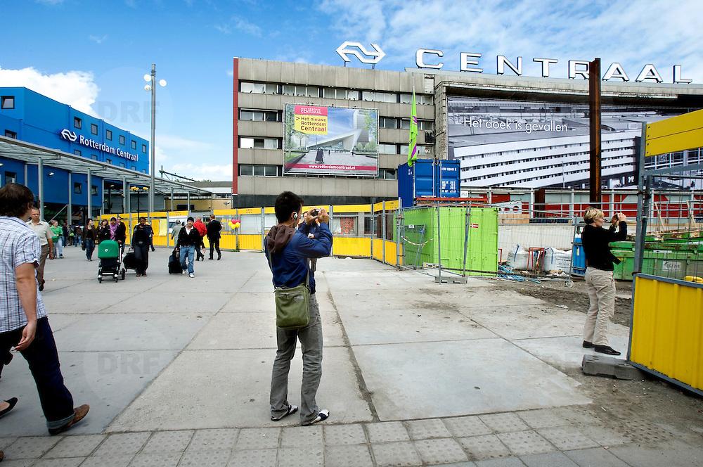 """Nederland Rotterdam 3 september 2007 20070903 ."""" Het doek is gevallen """" Zondag 2 september is het doek letterlijk doek gevallen voor het in 1957 geopende gebouw. Over enkele weken wordt de schepping van architect Sybold van Ravesteyn gesloopt en komt op het Stationsplein een nieuwe OV-terminal, die na 2011 ruim 300.000 reizigers per dag moet kunnen verwerken. Voorbijgangers maken een foto van het oude bekende centraal station, dat sinds 1957 dienst heeft gedaan. Een gloednieuw station zal op deze plek verrijzen. Op de achetrgrond links het tijdelijke centraal station. ..Het tijdelijke station dat de periode overbrugt tussen de sloop van het oude Rotterdam CS en de bouw van een nieuw station, kost 12 miljoen euro. Dat is een schijntje vergeleken met het half miljard waarop het nieuwe is begroot. De bedoeling is dat de tijdelijke bebouwing in februari klaar is. Het blijft open tot 2010. Het oude gebouw maakt plaats voor vijf tijdelijke. Daarvan zijn er vier voor de reizigers en een voor het personeel van de Spoorwegpolitie. ..Tijdelijk Rotterdam Centraal.1 september 2007..Alle treinreizigers opgelet! Vanaf 2 september sta je voor een dichte deur als je bij Rotterdam Centraal op de trein wilt stappen. Tenzij je de ingang van het tijdelijke Rotterdam Centraal al gevonden hebt. ..Naast het oude vertrouwde station staat al een tijdje een groot blauw gebouw en vanaf 2 september kun je daar op je trein stappen. Je kunt er zelfs een kopje koffie halen, of kleine boodschappen doen. Alle winkels zijn namelijk gewoon verplaatst naar het grootste tijdelijke station van Nederland...Het Centraal Station was al een hele tijd een grote bouwput, want er wordt heel hard gewerkt aan een nieuw, beter en vooral moderner station. Maar omdat afscheid nemen altijd zo moeilijk is, vindt er op 12 september een soort ode aan het station en de architect Sybold van Ravesteyn plaats. De letters Centraal Station worden omgetoverd tot Traan laten. De letters blijven nog enige tijd staan, waarna de"""