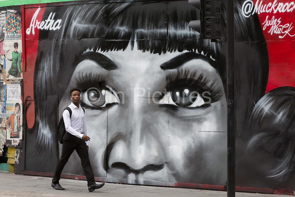 A Londoner walks past a recent mural in Shoreditch by artist Jules Muck of Soul Queen Aretha Franklin who died a few days earlier, on 20th August 2018, in London, England.