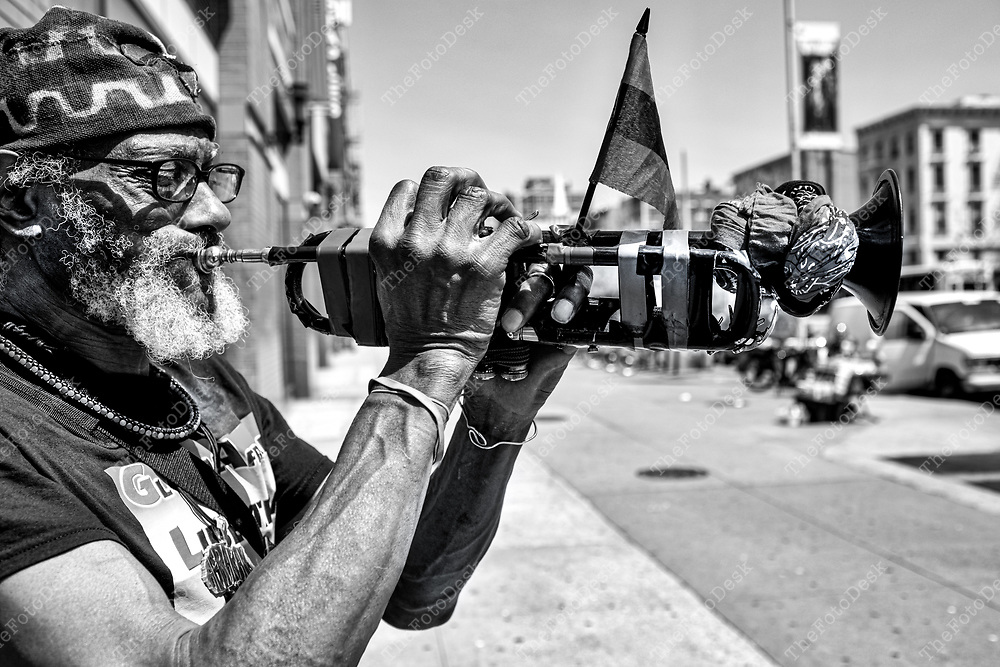 """HARLEM, New York: New Word Warrior appears on 125th street in Harlem. A regular fixture can be found playing """"The Black National Anthem'. (Left Every Voice)"""