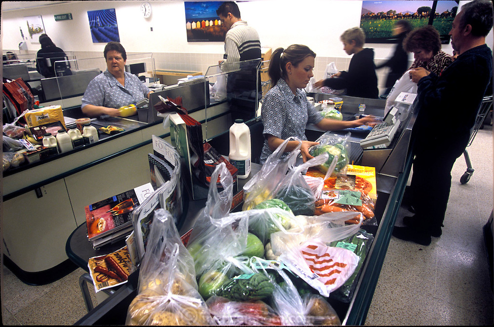 Three Baintons, Mark, Deb, and Josh, all wait at the checkout counter as they purchase a weeks' worth of food from their local Waitrose supermarket in  Collingbourne Ducis, Wiltshire, England. (Supporting image from the project Hungry Planet: What the World Eats.)
