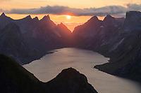 Midnight sun hangs low over mountains of Kirkefjord from summit of Reinebringen, Moskenesøy, Lofoten Islands, Norway