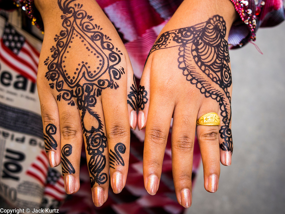 """08 AUGUST 2013 - BANGKOK, THAILAND: A woman shows her henna tattooed hands after Eid al-Fitr services at Haroon Mosque in Bangkok. Eid al-Fitr is the """"festival of breaking of the fast,"""" it's also called the Lesser Eid. It's an important religious holiday celebrated by Muslims worldwide that marks the end of Ramadan, the Islamic holy month of fasting. The religious Eid is a single day and Muslims are not permitted to fast that day. The holiday celebrates the conclusion of the 29 or 30 days of dawn-to-sunset fasting during the entire month of Ramadan. This is a day when Muslims around the world show a common goal of unity. The date for the start of any lunar Hijri month varies based on the observation of new moon by local religious authorities, so the exact day of celebration varies by locality.      PHOTO BY JACK KURTZ"""