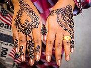 "08 AUGUST 2013 - BANGKOK, THAILAND: A woman shows her henna tattooed hands after Eid al-Fitr services at Haroon Mosque in Bangkok. Eid al-Fitr is the ""festival of breaking of the fast,"" it's also called the Lesser Eid. It's an important religious holiday celebrated by Muslims worldwide that marks the end of Ramadan, the Islamic holy month of fasting. The religious Eid is a single day and Muslims are not permitted to fast that day. The holiday celebrates the conclusion of the 29 or 30 days of dawn-to-sunset fasting during the entire month of Ramadan. This is a day when Muslims around the world show a common goal of unity. The date for the start of any lunar Hijri month varies based on the observation of new moon by local religious authorities, so the exact day of celebration varies by locality.      PHOTO BY JACK KURTZ"