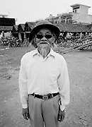 Older man with beard, hat and dark glasses stands in market