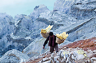 A sulphur miner carries his load out of the crater at the Kawah Ijen Sulphur Mines in East Java, Indonesia, Southeast Asia