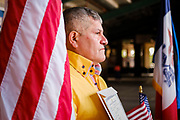 17 SEPTEMBER 2020 - DES MOINES, IOWA: ULISES ORO, originally from Honduras, poses for a portrait next to the American flag after a naturalization ceremony at Principal Park, a minor league baseball stadium in downtown Des Moines. About 75 people from 32 countries were naturalized as US citizens Thursday. It was the last citizenship ceremony in Des Moines before citizenship fees dramatically increase. Starting Oct. 2, the fee to apply for U.S. citizenship will increase from $640 to $1,160 if filed online, or $ 1,170 in paper filing, a more than 80% increase in cost. Advocates for immigration are afraid the new fees will be too expensive for many immigrants and say it's an effort by the Trump Administration to limit the number of new citizens welcomed into the United States. Because of the COVID-19 pandemic, there has been dramatic slow down in the number of naturalization ceremonies this year.           PHOTO BY JACK KURTZ