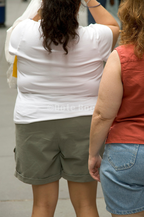 back view of two obese woman standing in the streets of New York City making a picture
