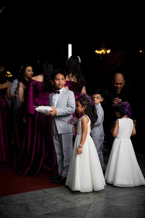A wedding procession waits for the ceremony to begin at the entrance to San Agustin Church, built in 1607 and located in the Intramuros district in Manila, Philippines. (July 27, 2019)