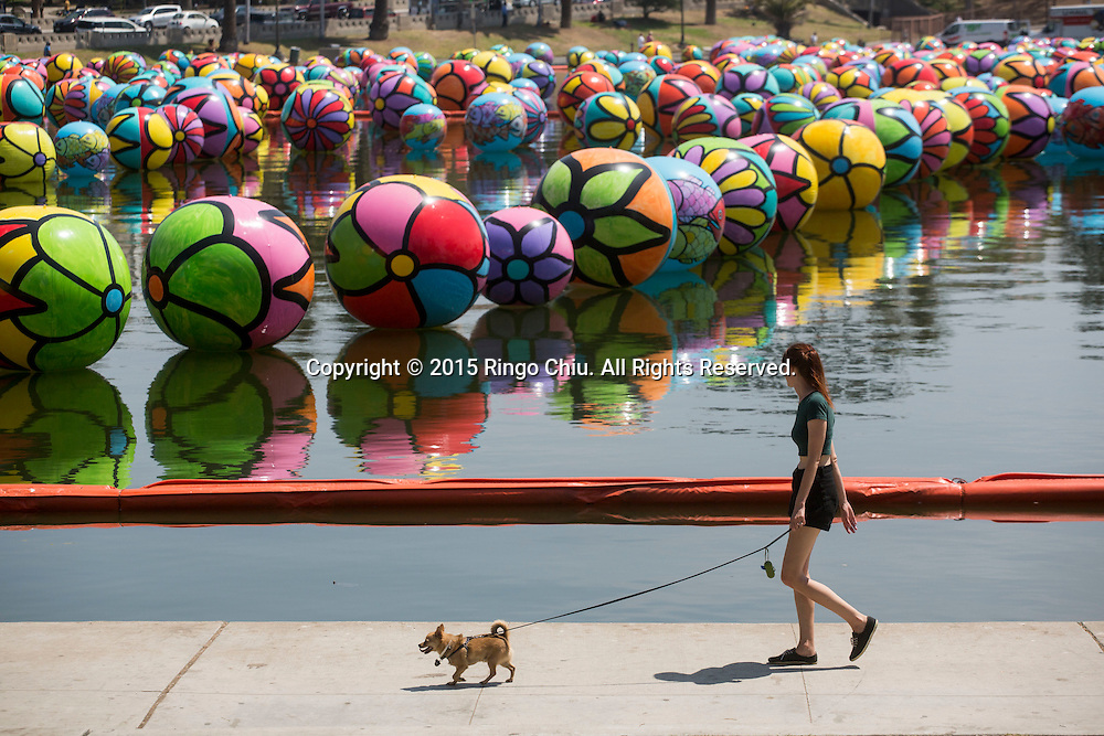 A woman walks her dog past the hand-painted vinyl balls floating in the MacArthur Park Lake as part of a large-scale public arts installation organized by the Portraits of Hope charity in Los Angeles, California on August 26, 2015. The work titled ``The Spheres at MacArthur Park,'' involves filling the park's 8.39-acre lake with about 3,000 balls, each 4 to 6 feet in diameter and covered in bright floral and fish patterns.(Photo by Ringo Chiu/PHOTOFORMULA.com)